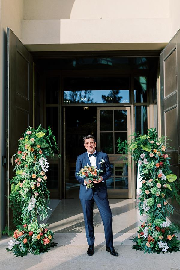 Εντυπωσιακός στολισμός εισόδου εκκλησίας με πλούσιες συνθέσεις από πρασινάδες και άλλα λουλούδια σε ζεστές αποχρώσεις