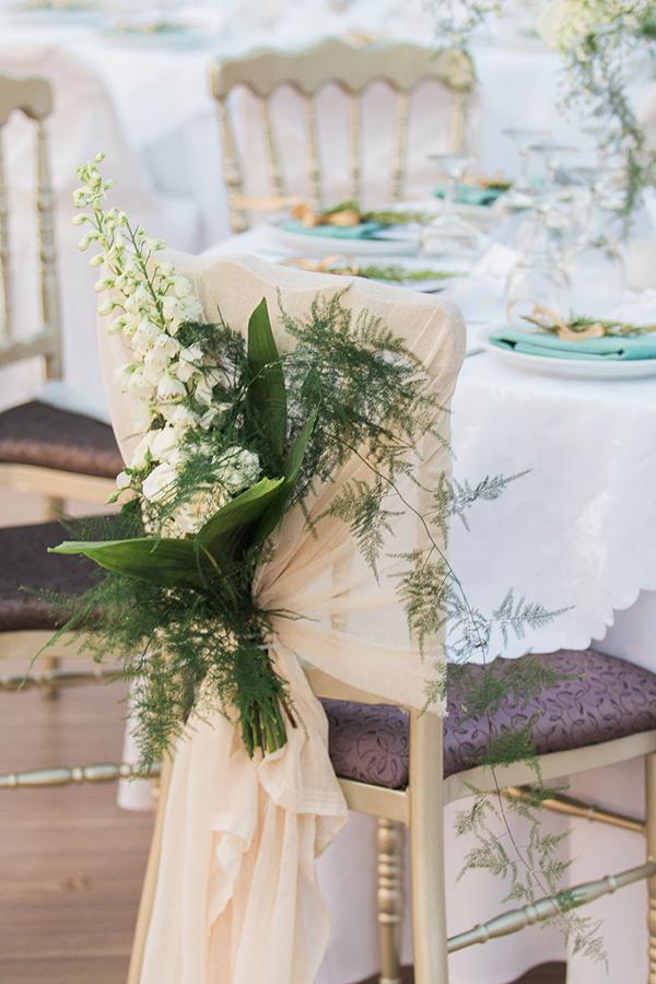 Εντυπωσιακός στολισμός γαμήλιας καρέκλας με λευκά άνθη και πλούσια πρασινάδα
