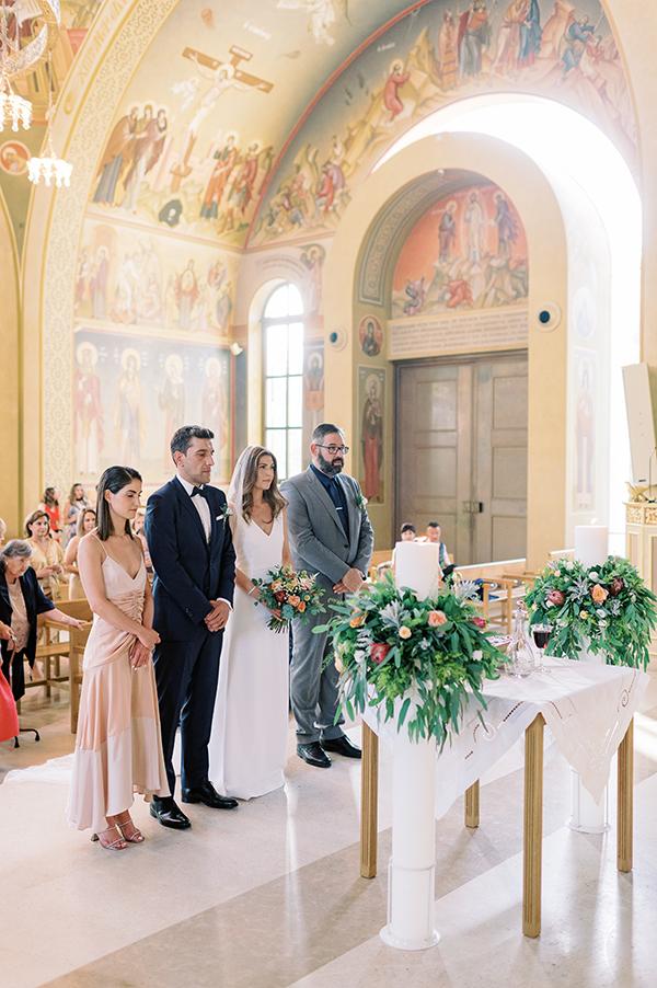 Λευκές λαμπάδες εκκλησίας διακοσμημένες με πλούσια πρασινάδα, πρωτέα και τριαντάφυλλα