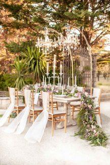 Ονειρικός στολισμός γαμήλιου τραπεζιού από πλούσιες πρασινάδες με ευκάλυπτο και τριαντάφυλλα σε απαλές ροζ και μωβ αποχρώσεις